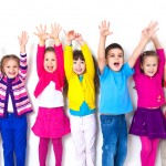 Seven kids in colorful clothing raising their both hands up